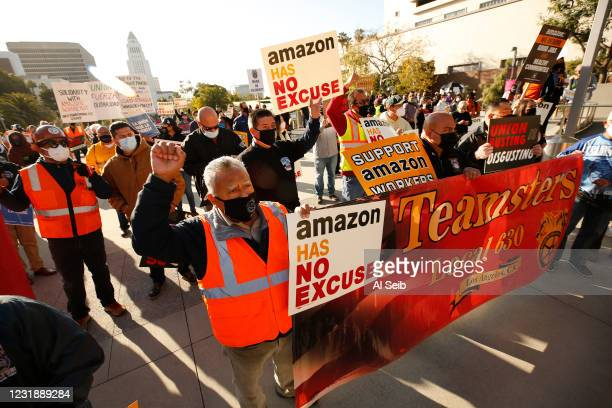 Jose Haro, Felipe Medina and Lou Villalvazo, left to right, with Teamsters Local 63 joined union workers as they rallied in downtown Los Angeles...