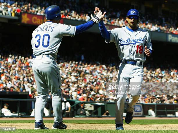 Jose Hernandez of the Los Angeles Dodgers is congratulated by Dave Roberts after scoring on a Robin Ventura hit in the eighth inning against the San...