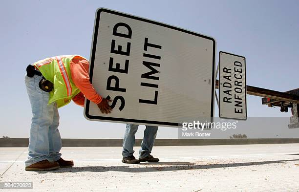 –Jose Ibarra and George Arsiniega tighten the nuts and bolts on a speed limit sign they are about to install on the 210 freeway extension project in...