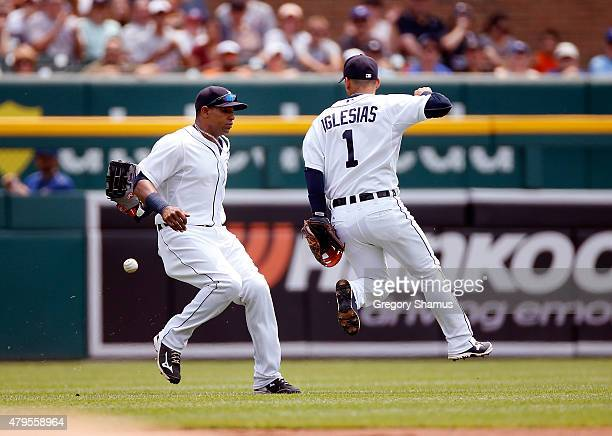 Jose Iglesias and Yoenis Cespedes of the Detroit Tigers can't get to a ball off the bat of Jose Reyes of the Toronto Blue Jays in the first inning at...