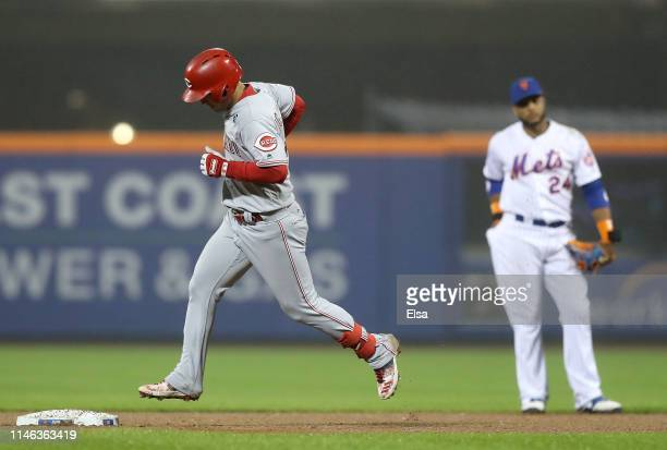 Jose Iglesias of the Cincinnati Reds rounds second base after he hit a solo home run in the ninth inning as Robinson Cano of the New York Mets stands...