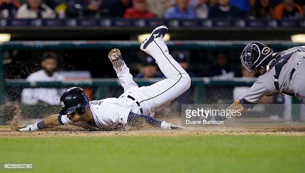 Jose Iglesias of the Detroit Tigers avoids the tag from catcher Kurt Suzuki of the Minnesota Twins to score from third base on a sacrifice fly hit by...