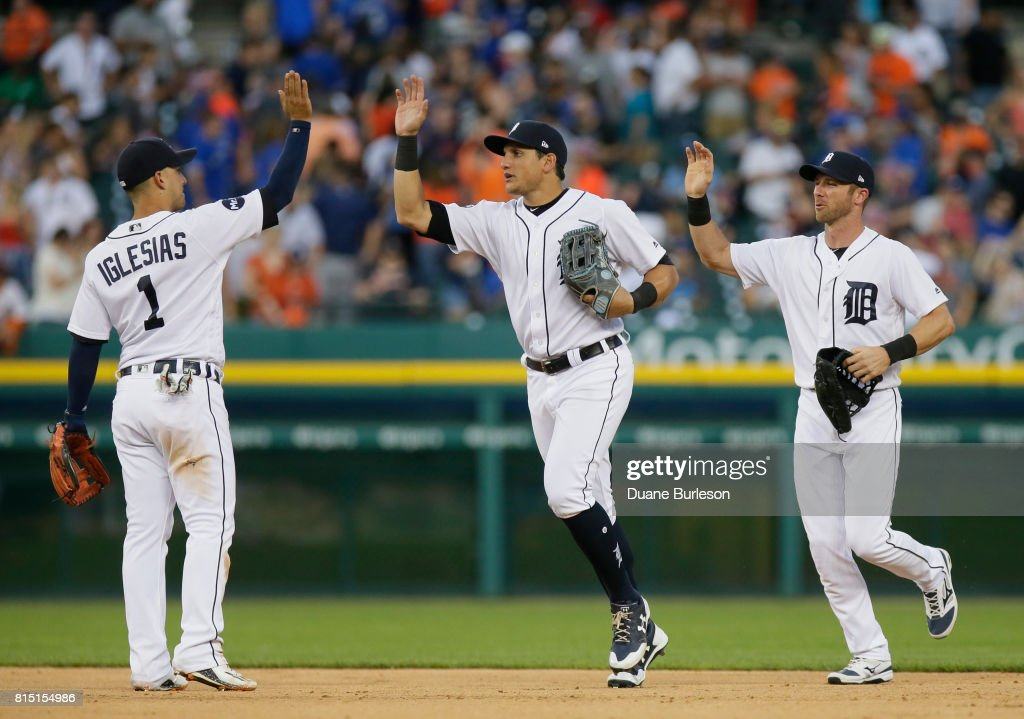 Jose Iglesias #1 of the Detroit Tigers celebrates a 11-1 win over the Toronto Blue Jays with Mikie Mahtook #15 of the Detroit Tigers and Andrew Romine #17 of the Detroit Tigers at Comerica Park on July 15, 2017 in Detroit, Michigan.
