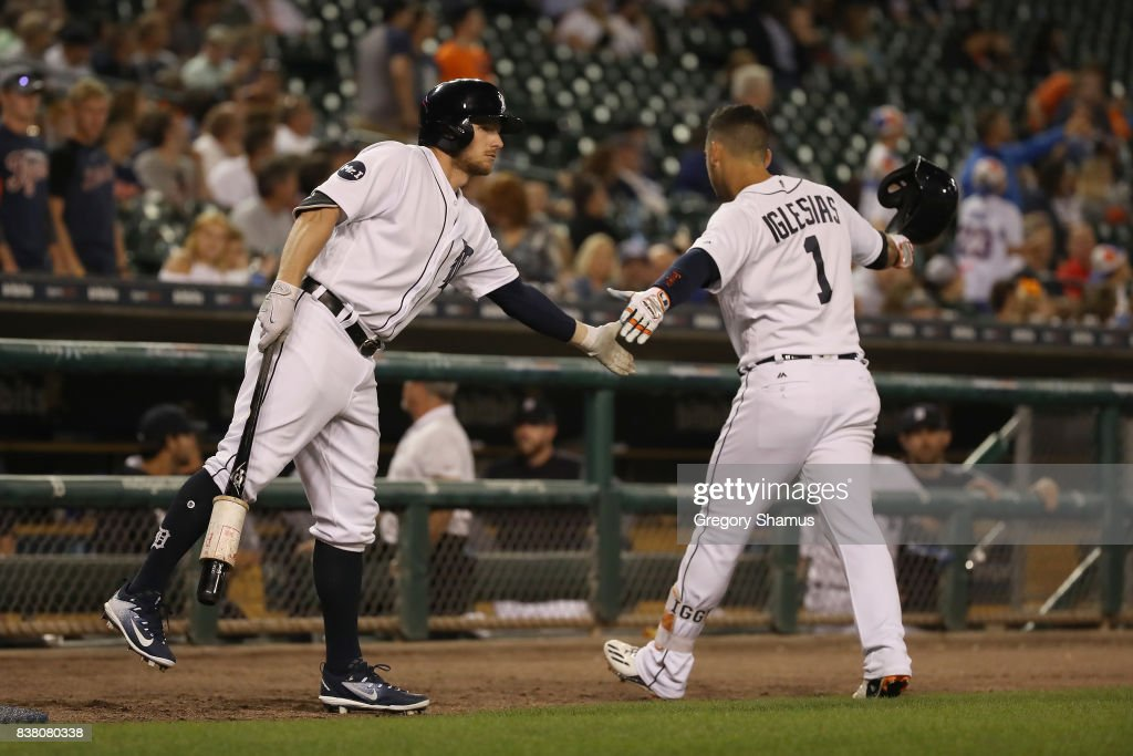 Jose Iglesias #1 of the Detroit Tigers celebrates a ninth inning home run with Alex Presley #14 while playing New York Yankees at Comerica Park on August 23, 2017 in Detroit, Michigan.