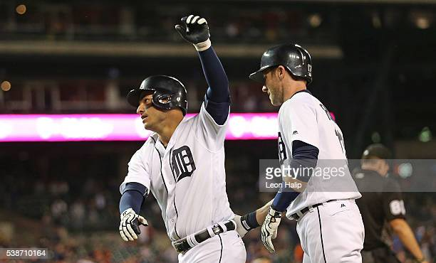 Jose Iglesias of the Detroit Tigers celebrates after scoring in the bottom of the ninth inning with teammate Andrew Romine during the game against...