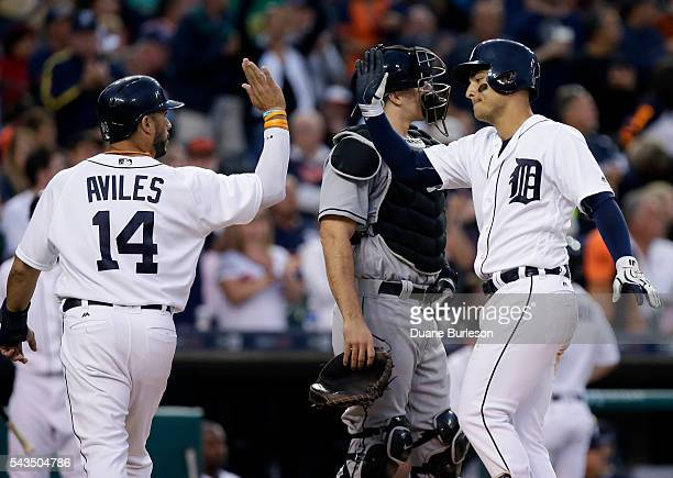 Jose Iglesias of the Detroit Tigers celebrates his tworun home run with Mike Aviles as they cross in front of catcher JT Realmuto of the Miami...