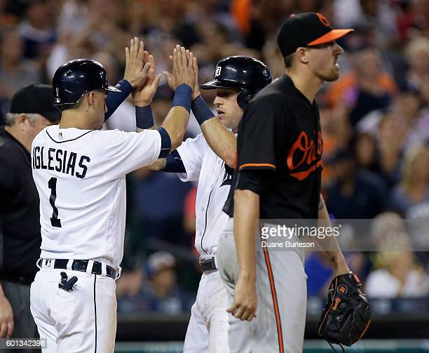 Jose Iglesias of the Detroit Tigers celebrates with Ian Kinsler of the Detroit Tigers after scoring on a single by JD Martinez as pitcher Kevin...