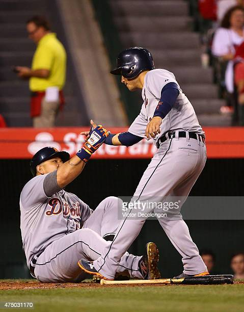 Jose Iglesias of the Detroit Tigers helps up teammate Miguel Cabrera after Iglesias scored and Cabrera was hit by a pitch in the third inning during...