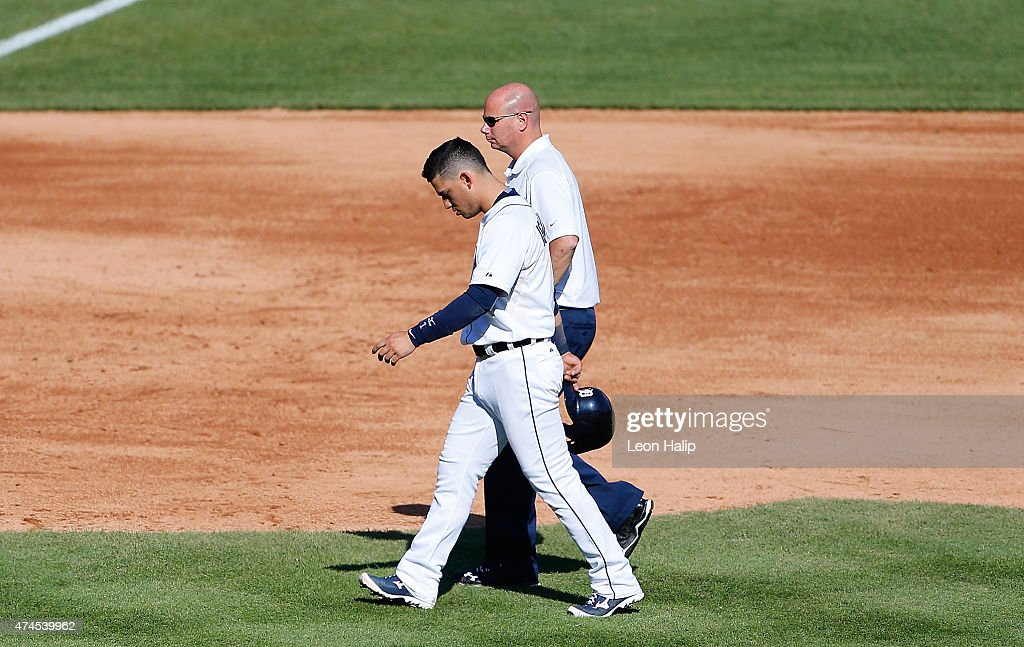 Jose Iglesias #1 of the Detroit Tigers is assisted off the field by Tigers trainer Doug Teter during the fifth inning of the game against the Houston Astros on May 23, 2015 at Comerica Park in Detroit, Michigan.