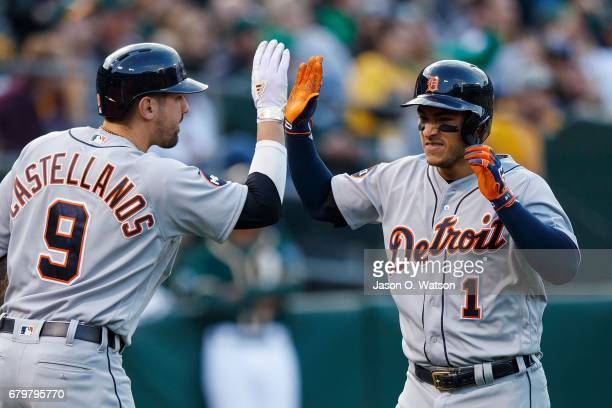 Jose Iglesias of the Detroit Tigers is congratulated by Nicholas Castellanos after scoring a run against the Oakland Athletics during the second...