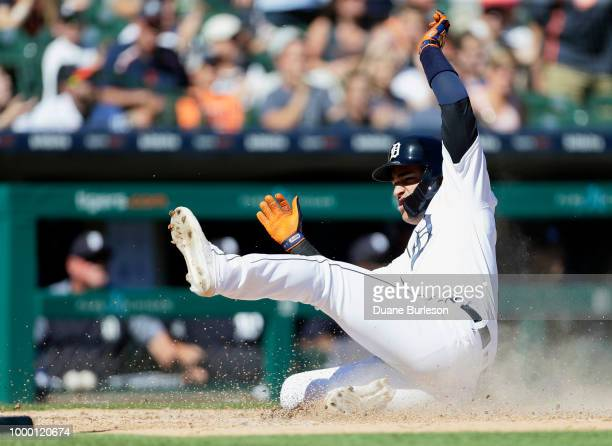 Jose Iglesias of the Detroit Tigers slides in safe at home plate one of three runs to score on an error by Delino DeShields of the Texas Rangers who...