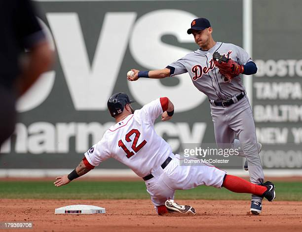 Jose Iglesias of the Detroit Tigers turns the double play against a sliding Mike Napoli of the Boston Red Sox in the second inning at Fenway Park on...