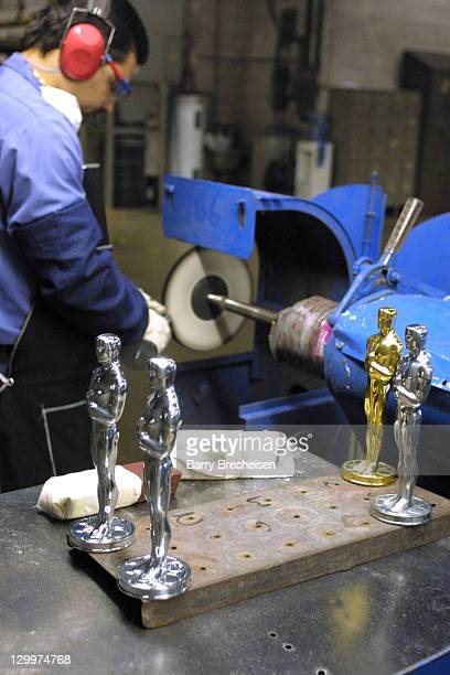 Jose Irizarry buffs an Oscar statuette at RS Owens and Company in Chicago
