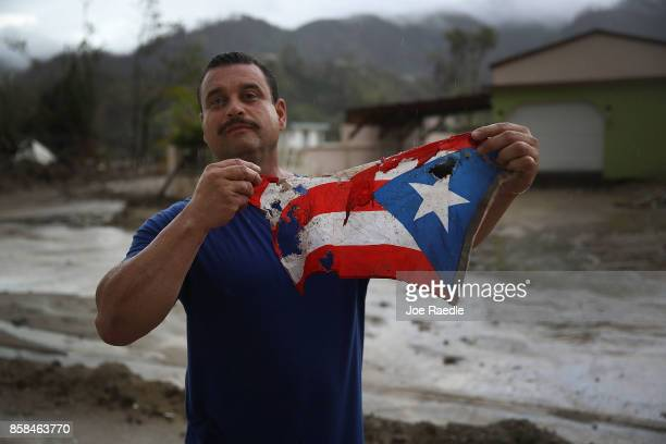 Jose Javier Santana holds a Puerto Rican flag he found on the ground after Hurricane Maria passed through on October 6, 2017 in Utuado, Puerto Rico....