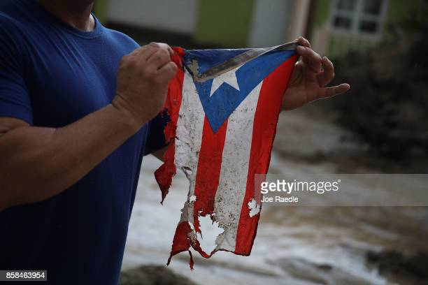 Jose Javier Santana holds a Puerto Rican flag he found on the ground after Hurricane Maria passed through on October 6 2017 in Utuado Puerto Rico Mr...