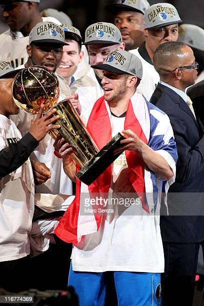 Jose Juan Barea of the Dallas Mavericks celebrates with the Larry O'Brien Championship trophy after the Mavericks won 105-95 against the Miami Heat...