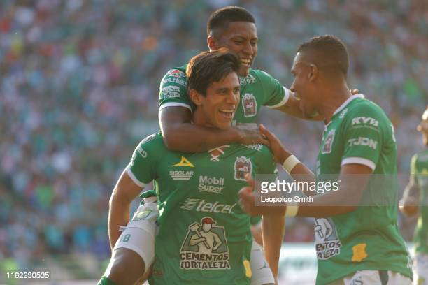 Jose Juan Macias of Leon celebrates with teammates after scoring the first goal of his team during the 5th round match between Leon and Chivas as...