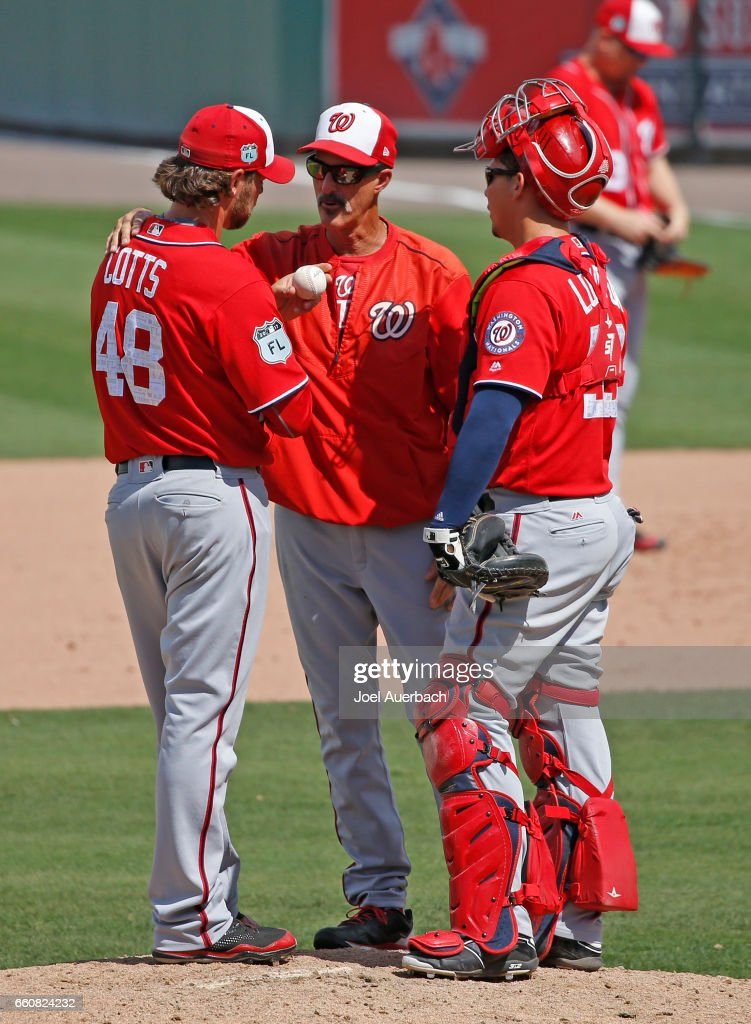 Jose Lobaton #59 looks on as pitching coach Mike Maddux #51 talks to Neal Cotts #48of the Washington Nationals during a break in action in the seventh inning of the spring training game against the Boston Red Sox at JetBlue Park on March 30, 2017 in Fort Myers, Florida. The Red Sox defeated the Nationals 8-1.