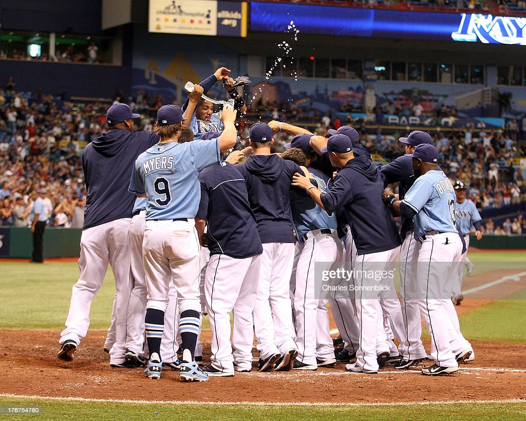 Jose Lobaton #59 of the Tampa Bay Rays is mobbed at home plate after hitting the winning homerun in the tenth inning against the Toronto Blue Jays during the game on August 18, 2013 at Tropicana Field in St. Petersburg, Florida.