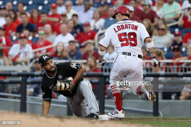 Jose Lobaton of the Washington Nationals is safe at first as Tomas Telis of the Miami Marlins bobbles the throw in the second inning at Nationals...