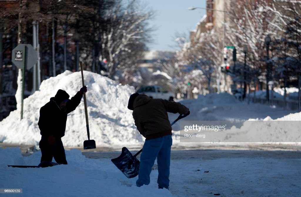 Jose Lopez, left, clears a sidewalk in Washington, D.C. U.S., on Monday, Feb. 8, 2010. A new storm system barreling across the country may bring as much as 12 inches (30 centimeters) of snow to New York, Washington and Baltimore starting late tomorrow, forecasters said. Photographer: Andrew Harrer/Bloomberg via Getty Images
