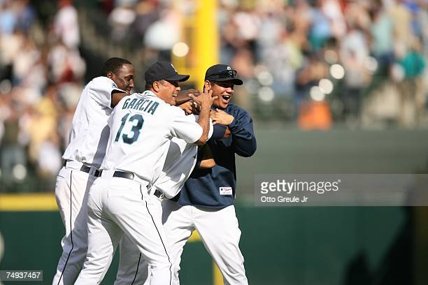 Jose Lopez of the Seattle Mariners is mobbed by Yuniesky Betancourt third base coach Carlos Garcia and pitcher Felix Hernandez after hitting the game...