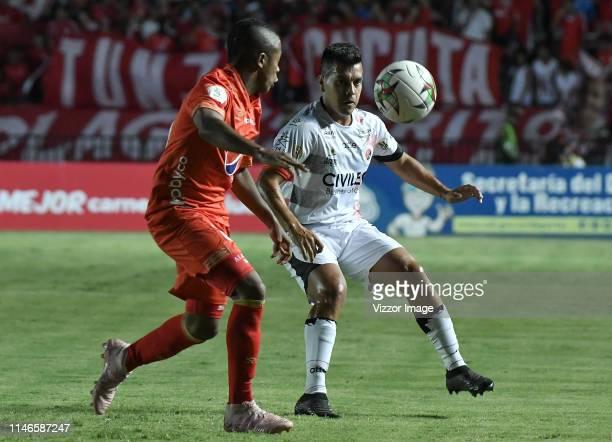 Jose Lugo of America struggles the ball with Matias Perez Garcia of Cucuta during the match between America de Cali and Cucuta Deportivo as part of...