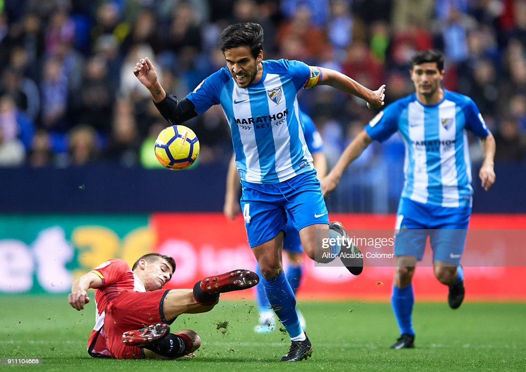 Jose Luis Garcia 'Recio' of Malaga CF (R) being fouled by Pere Pons of Girona FC (L) during the La Liga match between Malaga and Girona at Estadio La Rosaleda on January 27, 2018 in Malaga, .
