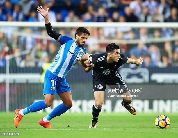 Jose Luis Garcia Recio of Malaga CF competes for the ball with Maximiliano Gomez of Celta de Vigo during the La Liga match between Malaga and Celta...