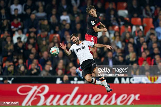 Jose Luis Gaya of Valencia CF competes for the ball with Santiago Arias of Atletico de Madrid during the La Liga match between Valencia CF and Club...