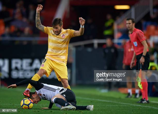 Jose Luis Gaya of Valencia competes for the ball with Cristian Portugues Manzanera of Girona during the La Liga match between Valencia and Girona at...