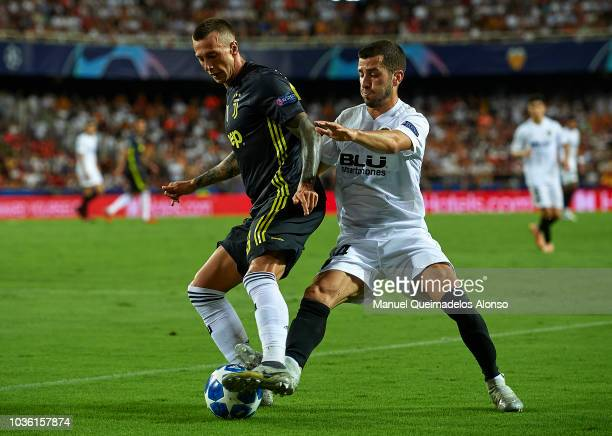 Jose Luis Gaya of Valencia competes for the ball with Federico Bernardeschi of Juventus during the Group H match of the UEFA Champions League between...