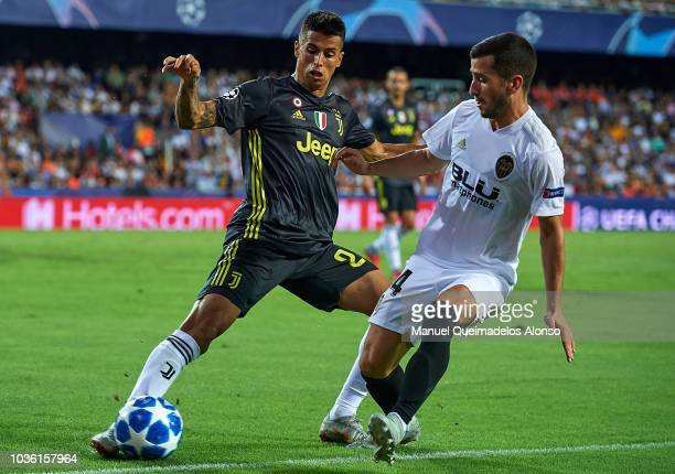 Jose Luis Gaya of Valencia competes for the ball with Joao Cancelo of Juventus during the Group H match of the UEFA Champions League between Valencia...