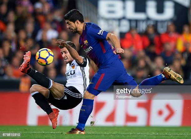 Jose Luis Gaya of Valencia competes for the ball with Luis Suarez of Barcelona during the La Liga match between Valencia and Barcelona at Estadio...