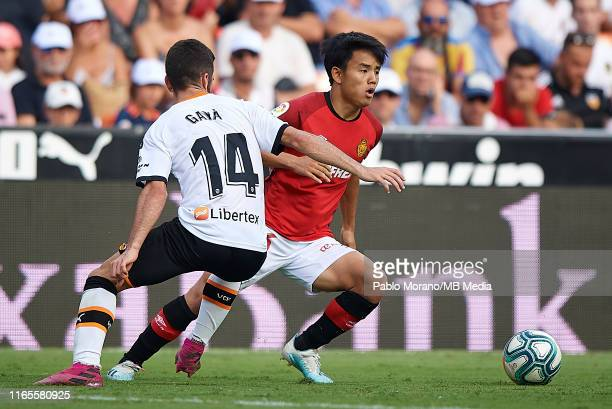 Jose Luis Gaya of Valencia competes for the ball with Takefusa Kubo of Mallorca during the Liga match between Valencia CF and RCD Mallorca at Estadio...