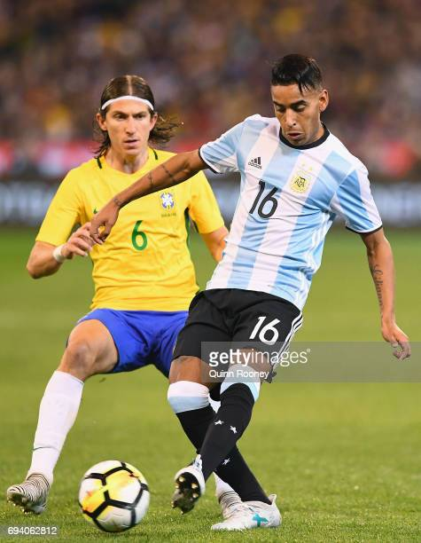 Jose Luis Gomez of Argentina passes the ball infront of Kasmirski Filipe Luis of Brazil during the Brazil Global Tour match between Brazil and...