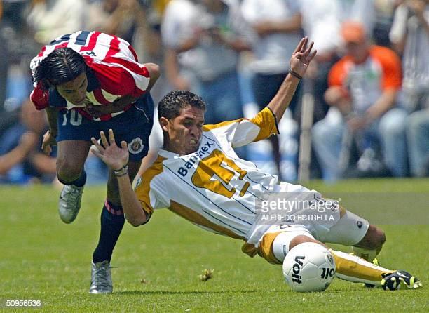 Jose Luis Lopez de los Pumas de la UNAM cae ante la marca de Alberto Medina de las Chivas de Guadalajara durante el partido final del torneo Clausura...