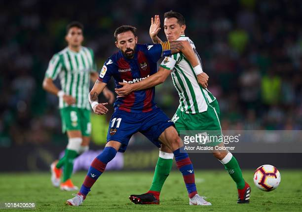 Jose Luis Morales of Levante UD competes for the ball with Andres Guardado of Real Betis Balompie during the La Liga match between Real Betis...