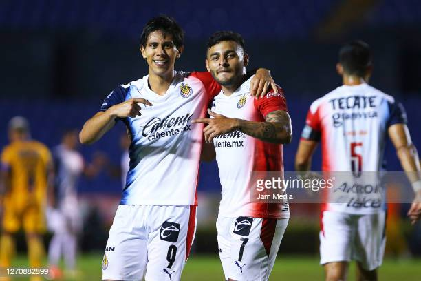 Jose Macias of Chivas celebrates with Alexis Vega after scoring the second goal of his team during the 8th round match between Tigres UANL and Chivas...