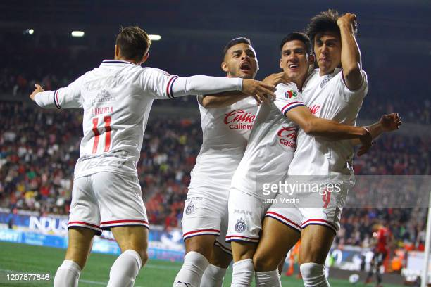 Jose Macias of Chivas celebrates with teammates after scoring the first goal of his team during the 7th round match between Tijuana and Chivas as...