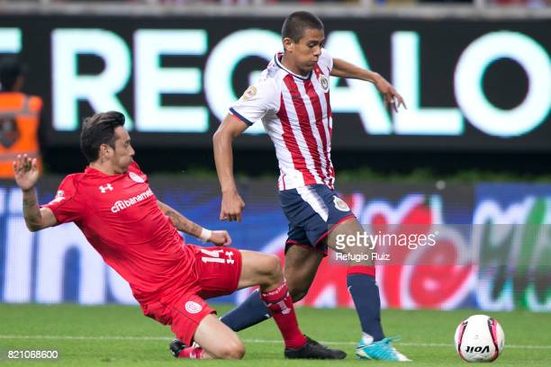 Jose Macias of Chivas fights for the ball with Rubens Sambueza of Toluca during the 1st round match between Chivas and Toluca as part of the Torneo...