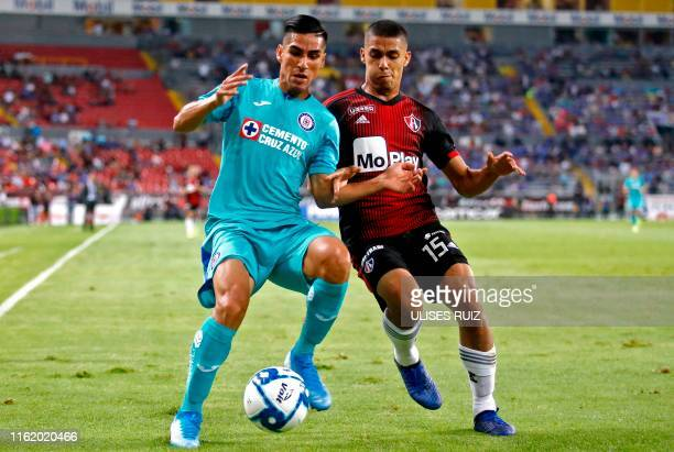 Jose Maduena of Cruz Azul and Diego Barbosa of Atlas vie for the ball during their Mexican Apertura football tournament match at Jalisco Stadium in...