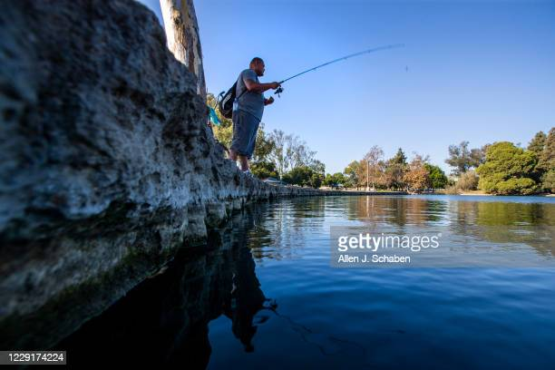 Jose Magaña, of Santa Ana, fishes under the shade of a tree for large mouth bass amidst a heat wave at Centennial Regional Park in Santa Ana Tuesday,...
