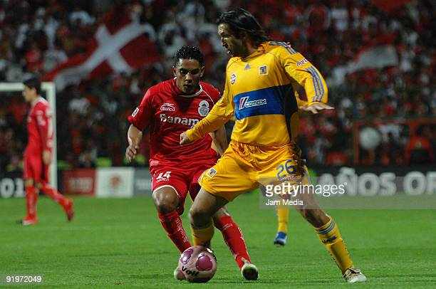 Jose Manuel Cruzalta of Toluca vies for the ball with Francisco Fonseca of Tigres during their match as part of the Mexican Football League at...