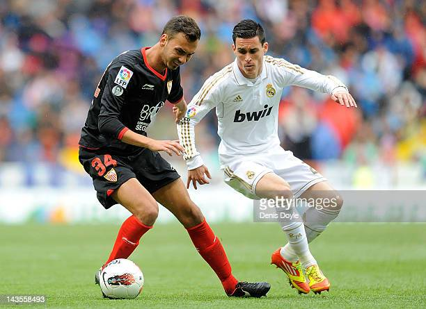 Jose Maria Callejon of Real Madrid CF battles for the ball against Deivid of Sevilla FC during the La Liga match between Real Madrid CF and Sevilla...
