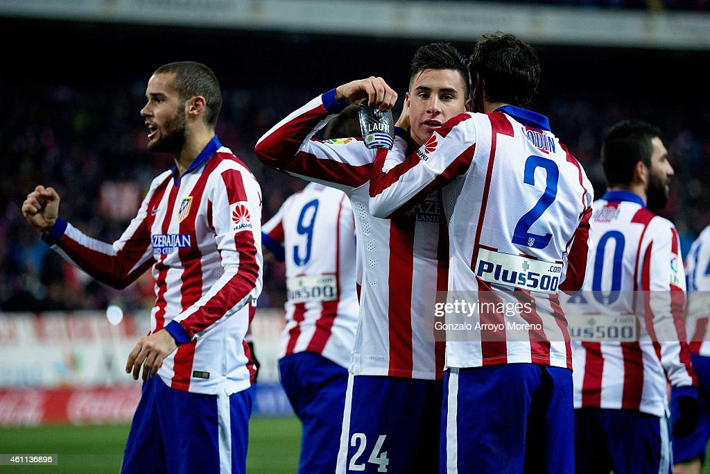Jose Maria Gimenez (L) of Atletico de Madrid shows his shinpad with the name Lauti printed on it as he celebrates scoring his second goal with his teammates Diego Godin (R) and Mario Suarez (L) during the Copa del Rey Round of 16 first leg match between Club Atletico de Madrid and Real Madrid CF at Vicente Calderon Stadium on January 7, 2015 in Madrid, Spain.