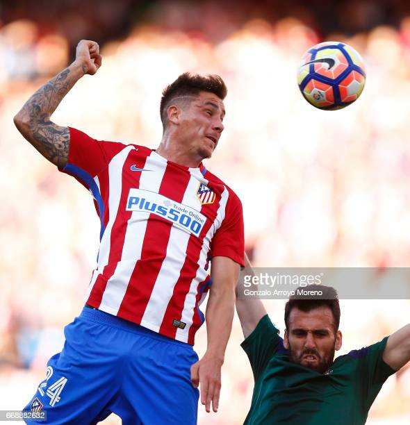 Jose Maria Gimenez of Atletico de Madrid wins the header after Juan Fuentes of CA Osasuna during the La Liga match between Club Atletico de Madrid...