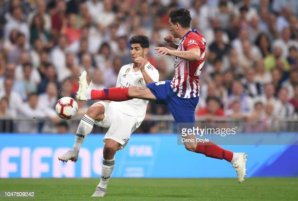 Jose Maria Gimenez of Club Atletico de Madrid cuts off Marco Asensio of Real Madrid during the La Liga match between Real Madrid CF and Club Atletico...