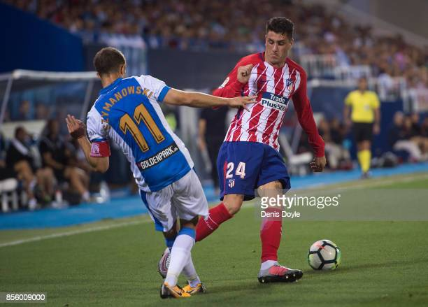 Jose Maria Gimenez of Club Atletico de Madrid is tackled by Alexander Szymanowski of CD Leganes during the La Liga match between Leganes and Atletico...