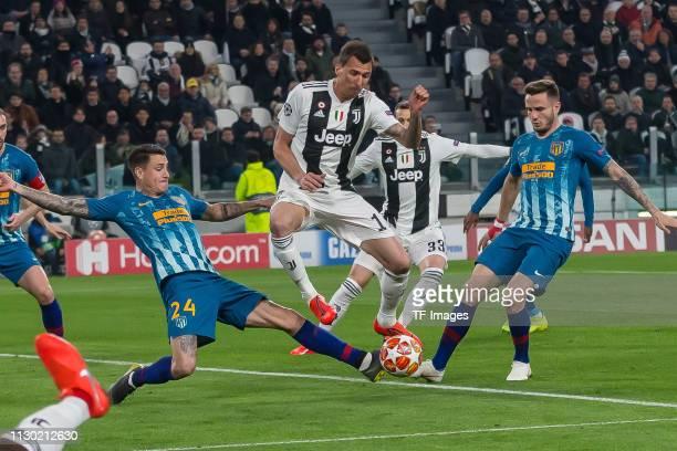 Jose Maria Gimenez of Club de Atletico Madrid Mario Mandzukic of Juventus and Saul Niguez of Club de Atletico Madrid battle for the ball during the...